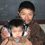 A father helps his young son as he is screened for hearing.