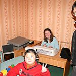 A young boy indicates he can hear the signals from audiologist Lisa Roselli. His mother looks on with a smile.